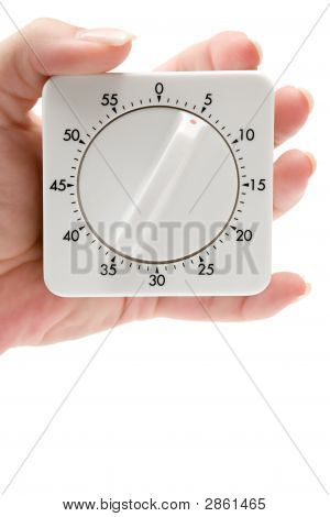 Female hand holding a timer. Isolated on a white background. stock photo