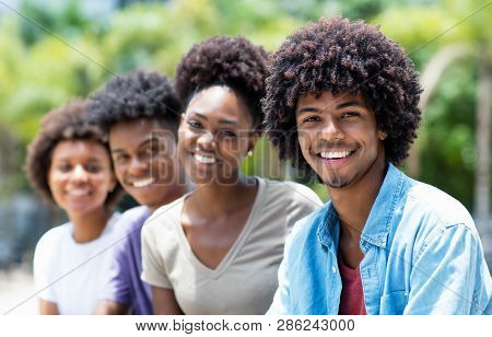 Handsome african american man with group of young adults in line outdoor in city in summer stock photo