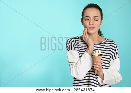 Emotional young woman with sensitive teeth and ice cream on color background. Space for text stock photo