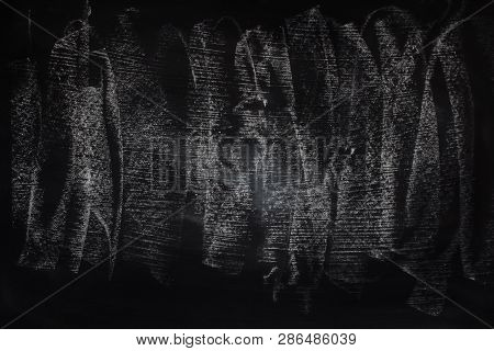 Abstract chalk rubbed out on blackboard or chalkboard background. Texture of a black chalkboard.Empty blank black chalkboard or chalk traces. Education and learning background with blackboard or chalkboard. Black chalkboard for sale offer advertising stock photo