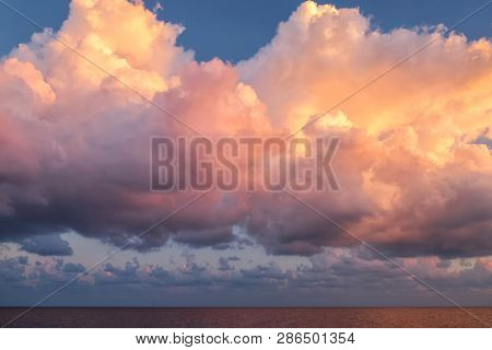 Giant pink cloud on a sunrise morning time floating over the sea after thunderstorm. stock photo