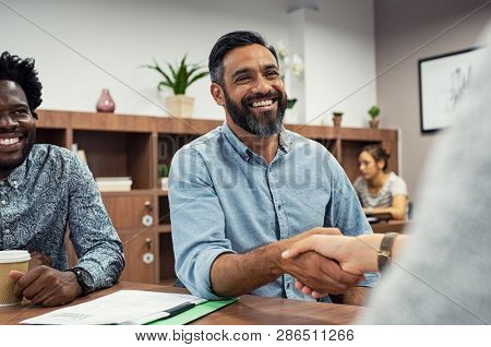 Two business people shaking hands while sitting in meeting room. Middle eastern businessman shake ha