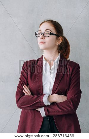 Company employee portrait. Ambitious business female. Young intern in glasses with crossed hands dreaming of success. stock photo