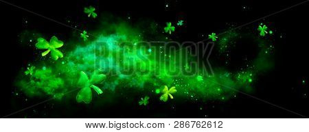 St. Patrick's Day abstract green background decorated with shamrock leaves. Patrick Day pub party celebrating. Abstract Border art design Magic backdrop. Widescreen clovers on black with copy space stock photo