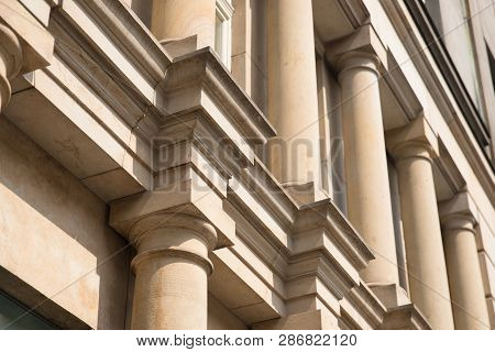 Stone columns of classical European style Doric capital close up. Play shadow and light, rhythm, meter stock photo