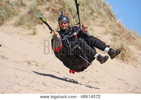 paraglider skimming the sand dunes of a beach ** Note: Slight blurriness, best at smaller sizes stock photo