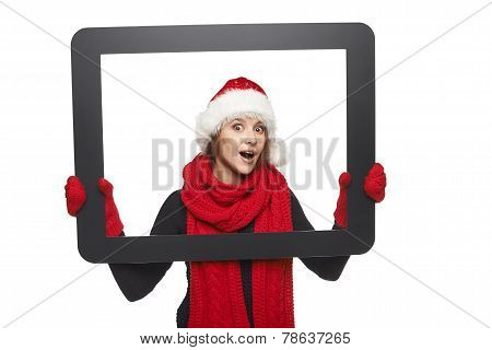 Surprised girl in Santa hat looking from TV computer screen, isolated on white background. stock photo