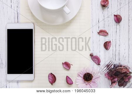 Flat lay stock photography purple flower petals glass bottle morden smart phone mock up ceramic coffee cup stock photo