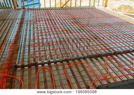 Modern manual laying of tuning water hydronic gas firing conduit supply on metal mesh insulation indoor new house room. Ground repair texture. Detail closeup macro view with space for text on grey net stock photo