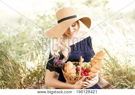 Smiling blonde girl 22-24 year old having picnic in park. Posing outdoors. Summer season. 20s. stock photo