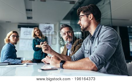 Young designer giving some new ideas about project to his partners in conference room. Business people discussing over new business project in office.