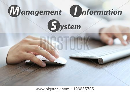 Concept of management information system. Businessman working with computer at wooden table, closeup stock photo