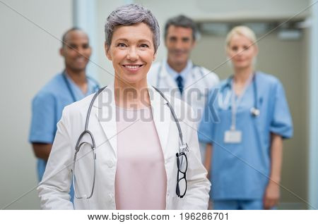 Portrait of smiling woman doctor standing in hospital with team in background. Senior female doctor