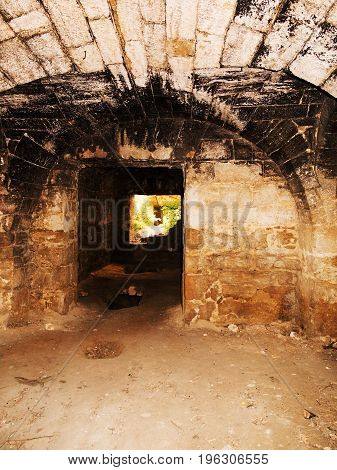 Mystic interior of an ancient dungeon. An old abandoned tunnel in an underground wine cellar. Entrance to catacombs. Dungeon An old stone fortress. As creative background for staging dark design. stock photo