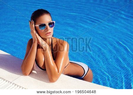 Beautiful tanned young woman with perfect body wearing white bikini and sunglasses relaxing in swimming pool. outdoor shot. copy space. stock photo