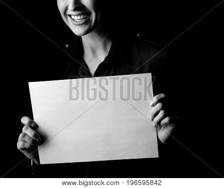 Сoming out into the light. Closeup on smiling woman in the dark dress isolated on black background showing blank paper sheet stock photo