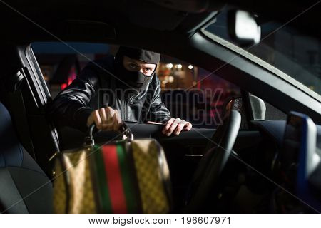 Male thief steals bag from car on parking stock photo