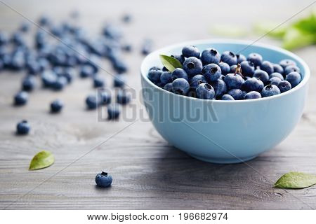 Small Bowl of Organic Blueberries on Wooden Table. Fresh blueberries in a small bowl on a rustic wooden table. stock photo