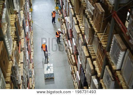Above view of warehouse workers moving goods and counting stock in aisle between rows of tall shelve