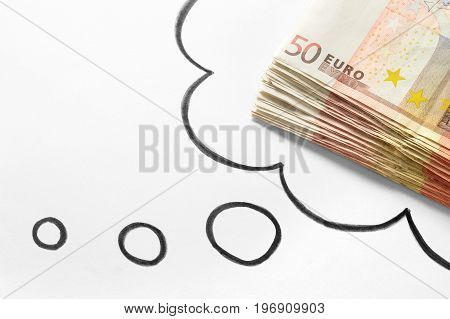 Thinking about money. Dreaming of rich and wealthy life. Money on mind. Lucrative new business idea. Hand drawn thinking speech bubble and thought cloud and a stack of 50 euro bills. stock photo