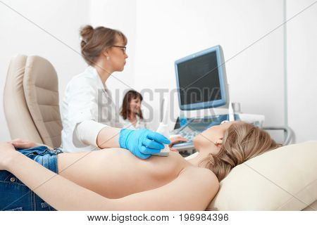 Cropped close up of a topless woman getting breast sonogram at the gynecological clinic health feminine cancer awareness concept. stock photo