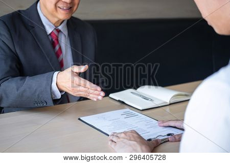 Employer or recruiter holding reading a resume during about colloquy his profile of candidate, employer in suit is conducting a job interview, manager resource employment and recruitment concept. stock photo