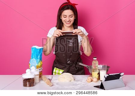 Young European pleasant woman makes photo of her half ready pie, post it in social networking sites. Cheerful attractive cute model poses in brown apron, white t shirt, and bright red headband. stock photo