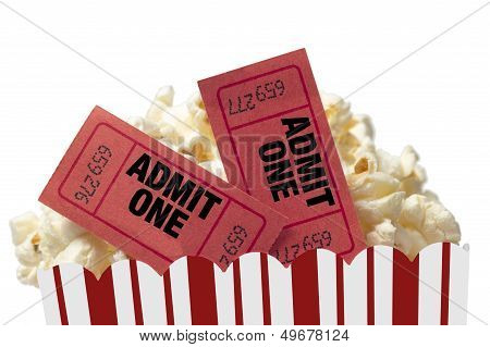 Close up shot of red movie tickets in a tub of delicious popcorn and shot on white background. stock photo