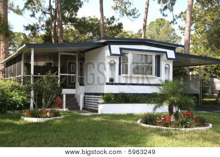 Pride of ownership shows in the lawn and garden in front of this older mobile home in a retirement community. stock photo