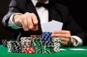 club, betting, poker, individuals and excitement idea - close up of poker player with playing ca