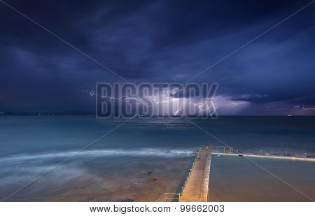 Views from Collaroy over the rockshelf and rockpool south of the beach towards the north east at the storms. Seeking shelter from the rain to capture this long exposure and yes that little figure was stretching and exercising in the rain.. stock photo