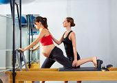 pregnant lady pilates reformer cadillac exercise workout with fitness coach