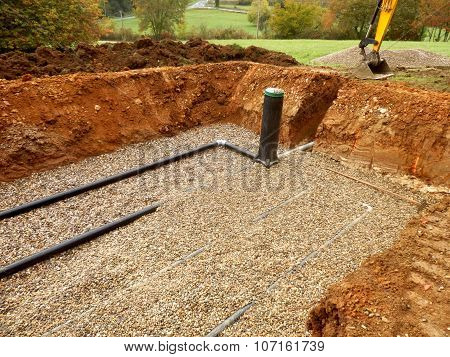 Bottom layer of pipework being covered in gravel, prior to the membrane and sand being applied, during the construction of a sand and gravel drainage system