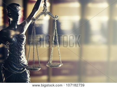 Burden of proof - Moodily lit legal law concept image with Scales of justice backlit and row of law