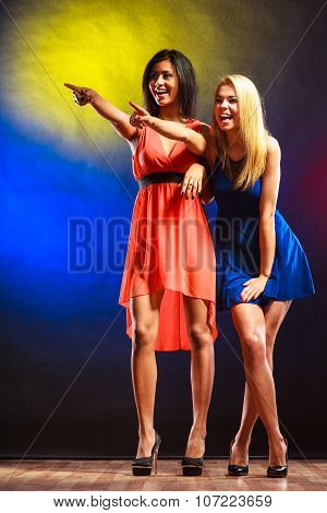 Party celabration carnival. Two attractive funny dancing women in dresses pointing on colorful background stock photo