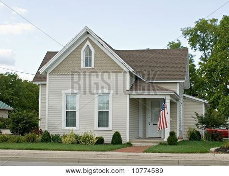 Small, one-story Mid-western house with American flag. stock photo