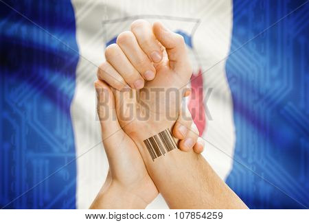 Barcode ID number tatoo on wrist and Canadian province flag on background - Northwest Territories stock photo