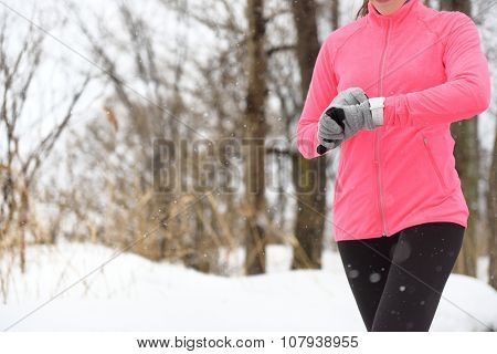 Runner using smartwatch jogging in snow trail in forest. winter weather closeup. Female athlete chec