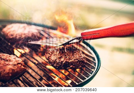 Tasty meat on the grill outdoors, preparing barbecue pork for burgers, traditional summer food cooko
