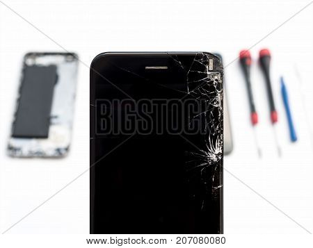 Close-up of cracked smartphone screen on blurred smartphone component background stock photo