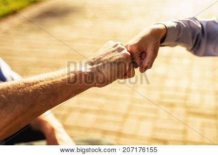 Bro fist. The old man greets his grandson with a bro fist. Close up photo. stock photo
