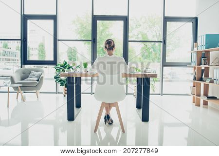 Authority development feminity concept. Full length rear view of pretty business woman sitting at her light modern work station checking e mails in trendy outfit and shoes with hairdo stock photo