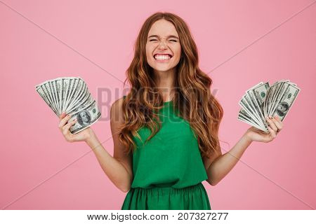 Portrait of a satisfied happy woman winner with long hair holding bunch of money banknotes in each h