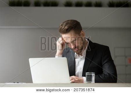 Perplexed, puzzled handsome businessman looking at laptop screen at workplace in office. Young CEO or project manager is not sure whether he should agree to the deal, sign contract, buy stock shares. stock photo