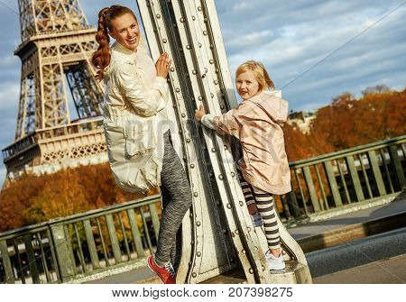 Year round fit & hip in Paris. smiling healthy mother and daughter in sport style clothes on Pont de Bir-Hakeim bridge in Paris having fun time stock photo