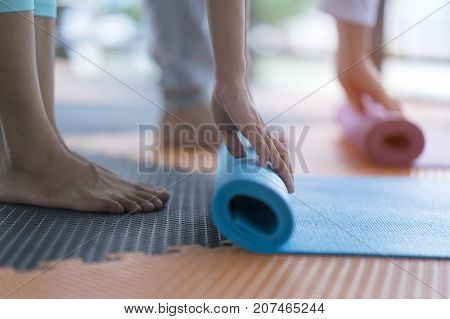 Yoga practitioner folding yoga mat after class at studio. Workout lifestyle for meditation body balance vs body strength. Yoga mat is equipment support practitioner during workout. Healthcare concept stock photo