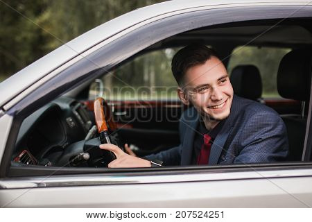 Successful business man in a dark business suit in the car. Stylish man in car. Young driver in car. Sitting behind the wheel of a new car. A man is smiling in the car. To drive car stock photo