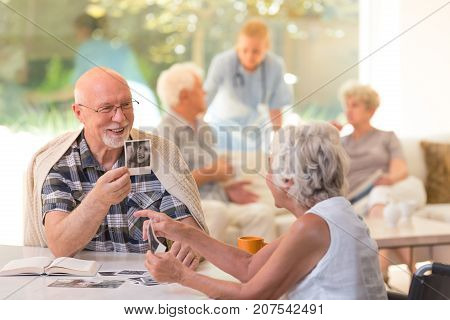 Husband in glasses sitting by the table and showing old photos to his wife with Alzheimer's disease at the rest home stock photo