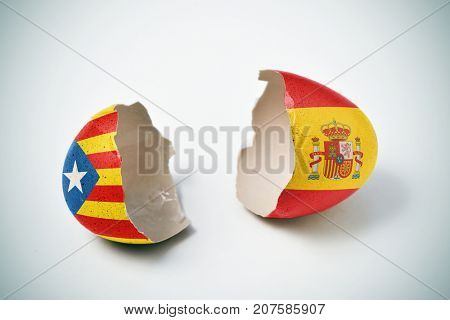 the two halves of a cracked eggshell, one patterned with the Estelada, the Catalan pro-independence flag and the other one patterned with the flag of Spain stock photo