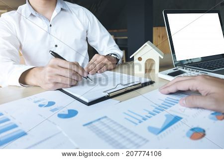 Man sign a home insurance policy on home loans Agent holds loan and investment chart graph documents table installment payment Real Estate concept. stock photo
